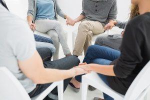 люди держатся за руки в центре психологической реабилитации