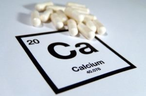 горсть таблеток на фоне химического обозначения кальция