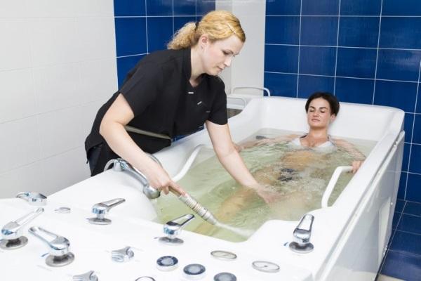 Пациентка погружается в радоновую ванну до уровня сосков
