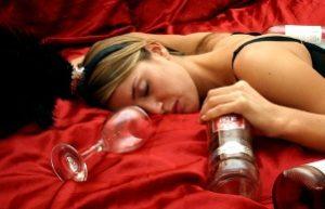 пьяная женщина спит с бутылкой алкоголя