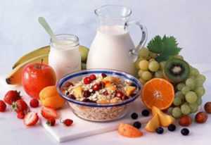 на столе фрукты, овсяная каша и молоко