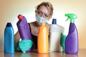женщина занимается уборкой в резиновых перчатках и маске